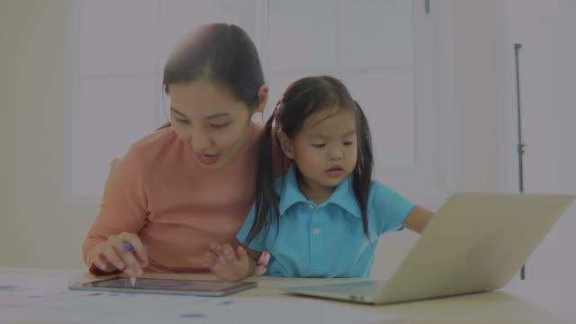 mor med småbarn dotter arbetar på laptop i köket - working from home bildbanksvideor och videomaterial från bakom kulisserna