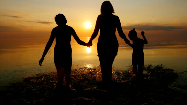 Mother with two children go swimming in the sea at sunset, laughing video