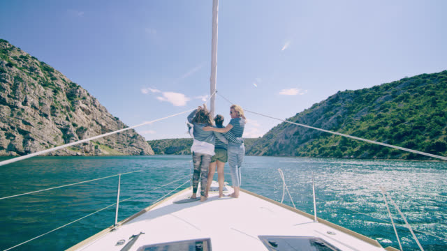 WS la madre con dos hijas en una cubierta de un velero navegando en la bahía de - vídeo