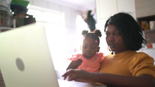mor som arbetar hemma och tar hand om sin dotter - flickbaby bildbanksvideor och videomaterial från bakom kulisserna