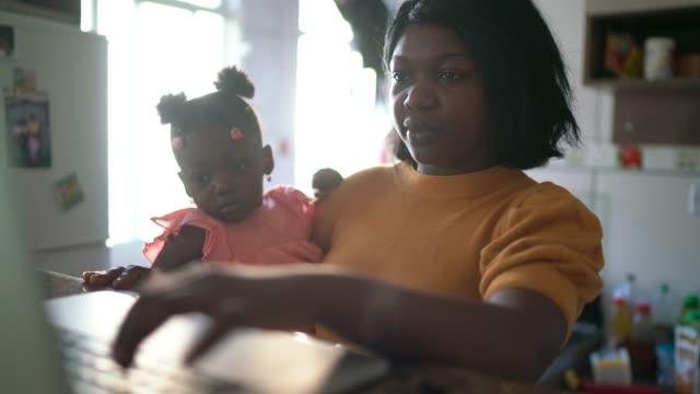 stockvideo's en b-roll-footage met moeder die thuis werkt en van zijn dochter geeft - alleenstaande moeder