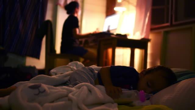 vidéos et rushes de mère travaillant à la maison avec le sommeil de fils - travaux maison