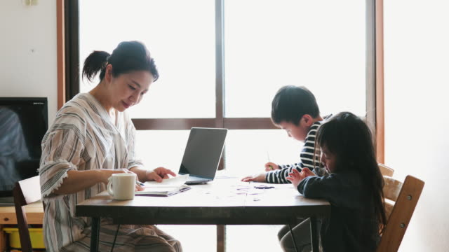 Mother working from home with children Asian mother is working with laptop while her son and daughter are studying in the living room. life balance stock videos & royalty-free footage