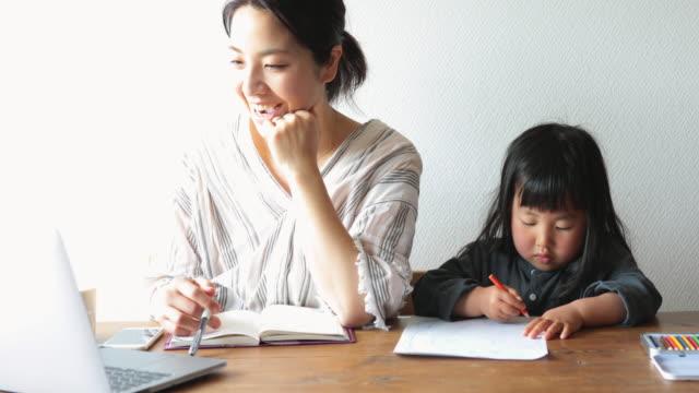 母は娘と自宅で働く - テレビ会議 日本人点の映像素材/bロール