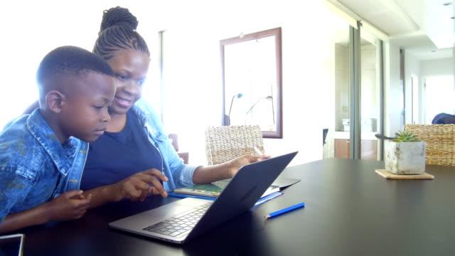 vidéos et rushes de mère travaillant de la maison avec fils - femmes actives
