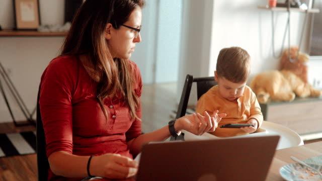 stockvideo's en b-roll-footage met moeder werkt op de laptop in de keuken terwijl haar zoon horloges cartoon op haar telefoon - oil kitchen
