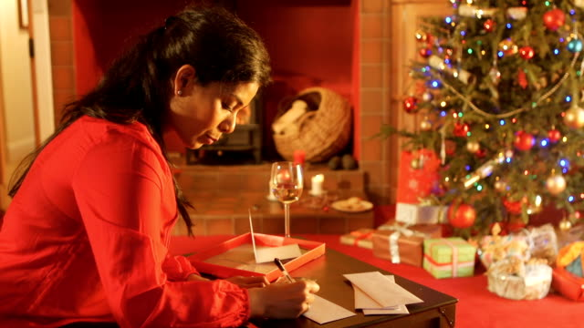 Mother Writing Christmas Cards in the Living Room Mother writing Christmas cards by the fire place in the living room while enjoying a glass of wine indian family stock videos & royalty-free footage