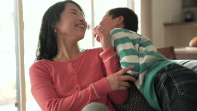 vidéos et rushes de fre mère et fils se détendre dans le salon, canapé-lit - seulement des japonais