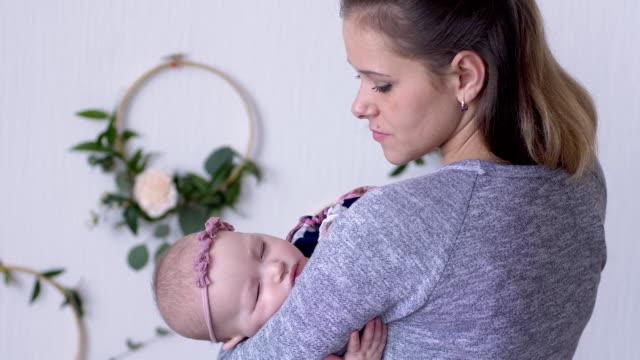 stockvideo's en b-roll-footage met moederschap, mama houdt en knuffelen meisje van de baby in haar armen binnenshuis close-up - background baby