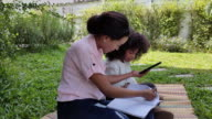 istock Mothers and children are resting and studying online at garden park. 1263171132