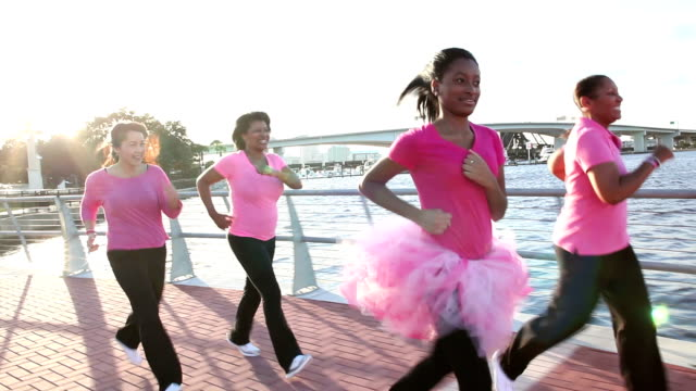mothers and daughters running for breast cancer charity - tutù video stock e b–roll