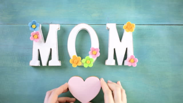 Mother's Day White letters MOM on a painted wood background. mothers day stock videos & royalty-free footage