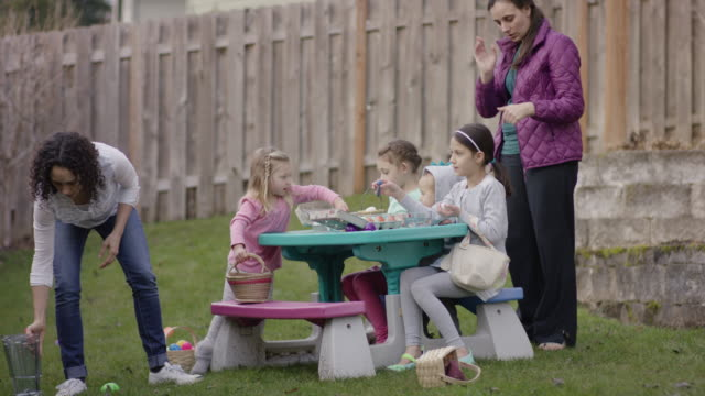 Mothers helping their children decorate Easter eggs video