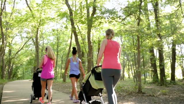 Mothers in running club pushing strollers and talking to instructor at park video