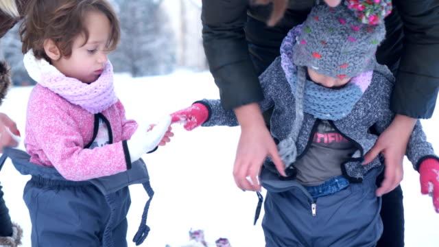 mothers prepare daughters for snow - abiti pesanti video stock e b–roll