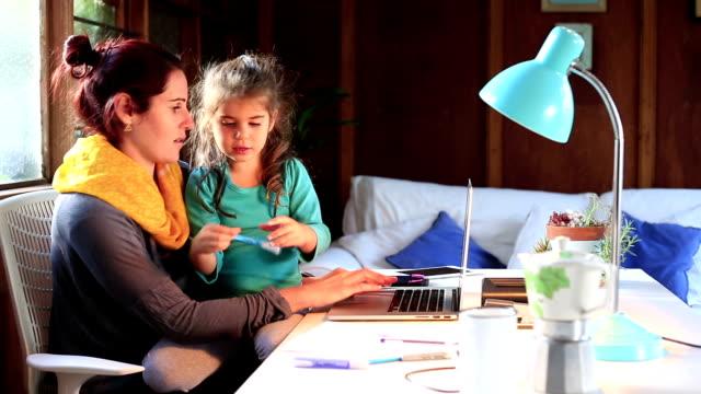 Luttes des mères au travail tandis que sa petite fille s'assoit sur ses genoux - Vidéo