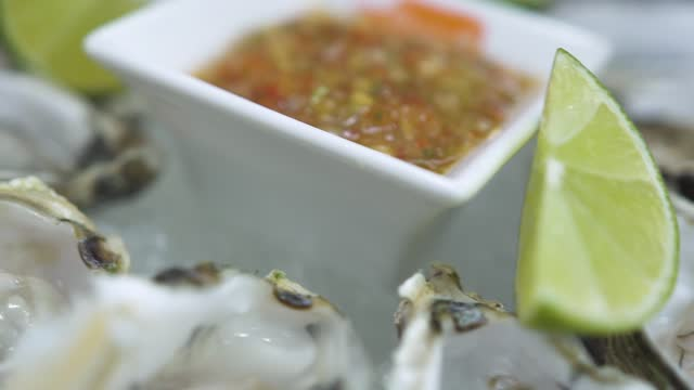 Motion above oysters and sauce with lime slices on ice