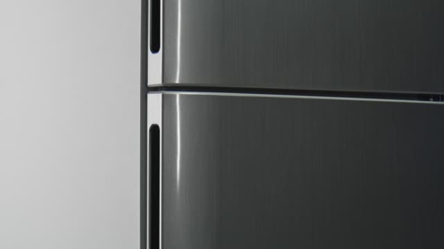 motion along modern grey refrigerator with closed doors motion along modern grey domestic refrigerator with closed doors at bright light close view handle stock videos & royalty-free footage