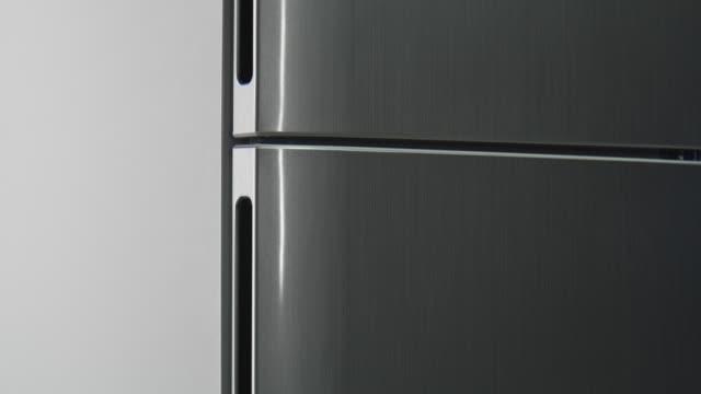vídeos y material grabado en eventos de stock de movimiento a lo largo de la nevera gris moderna con puertas cerradas - manija
