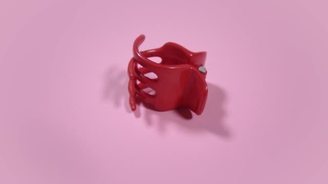 motion around red plastic kid claw clip on pink background - аксессуар для волос стоковые видео и кадры b-roll