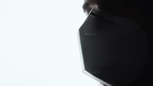 движение крупным планом портрет человека, глядя в сторону и носить kn95 маски для защиты. - covid testing стоковые видео и кадры b-roll