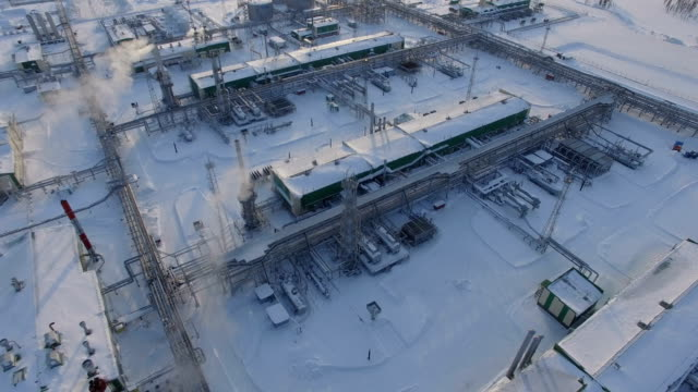 Motion from above to Large Refinery Plant Area among Snow