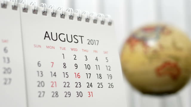 Motion of August 2017 calendar with blur earth globe turning background video