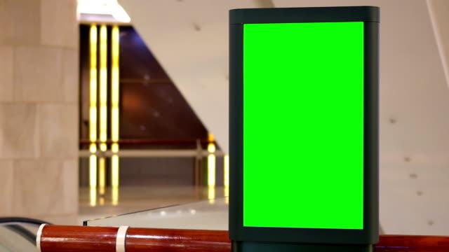 motion of big green screen billboard beside escalator inside shopping mall - poster стоковые видео и кадры b-roll