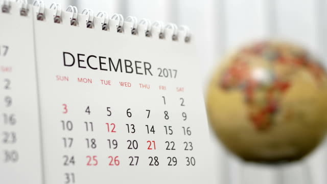 Motion of December 2017 calendar with blur earth globe turning background video