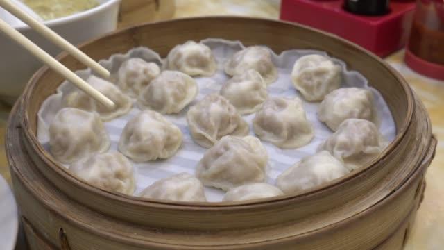 4k bewegung des essens xiao lange bao suppe knödelballen mit stäbchen in restaurant (traditionelle chinesische küche) in taipeh taiwan - kloß stock-videos und b-roll-filmmaterial