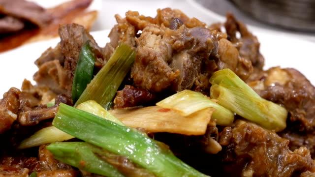 Bewegung von gebratenem Rindfleisch und grünen Zwiebeln auf dem Tisch in chinesischen Restaurant – Video