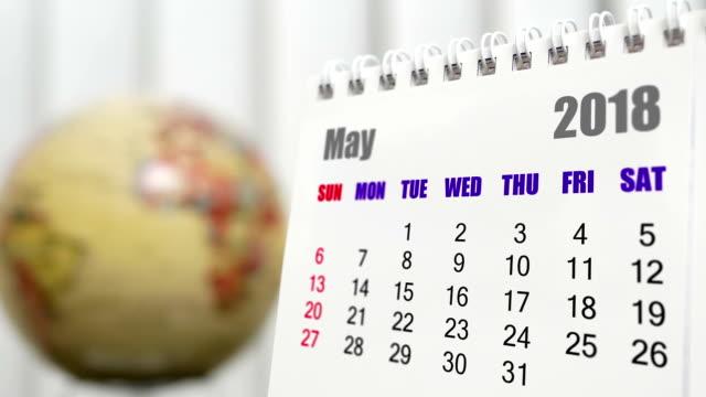 vidéos et rushes de motion de mai 2018 calendrier avec globe terrestre de flou en arrière-plan - 2018