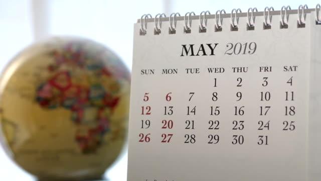 vídeos de stock e filmes b-roll de motion of may 2019 calendar with blur earth globe turning background - maio
