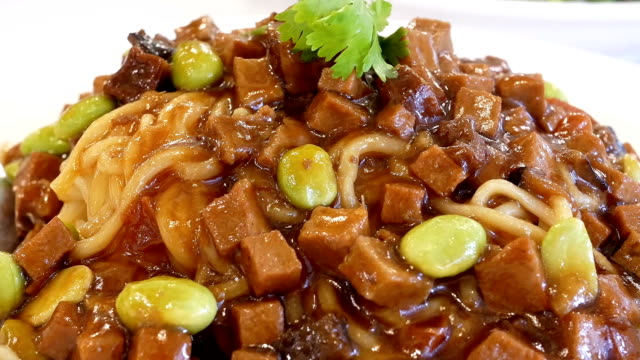 Motion of noodle with spicy bean sauce on plate inside Chinese restaurant video