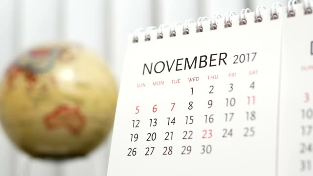 Motion of November 2017 calendar with blur earth globe turning background video