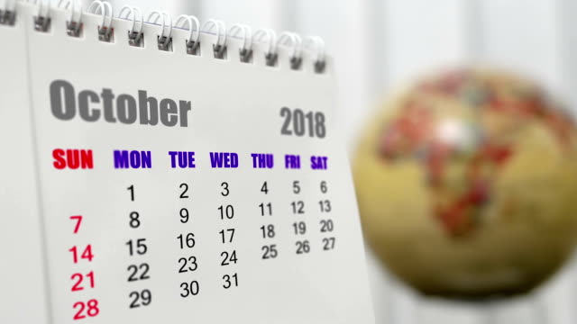 Motion of October 2018 calendar with blur earth globe turning background video
