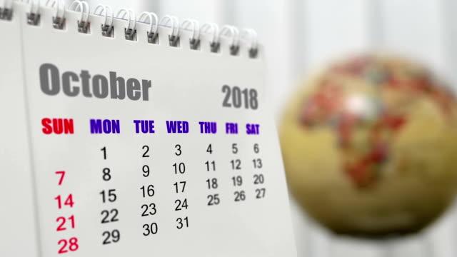 vidéos et rushes de motion d'octobre 2018 calendrier avec globe terrestre de flou en arrière-plan - 2018