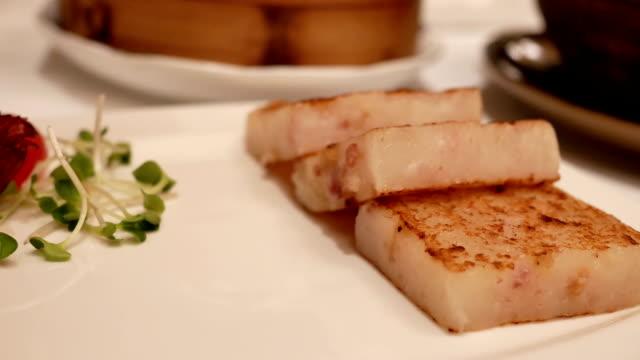 Motion of pan fried turnip cake dim sum inside restaurant video