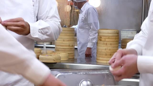 重い蒸気バスケットと餃子を作るに自分の手で生地を形成している人々 の動き - 中国料理点の映像素材/bロール