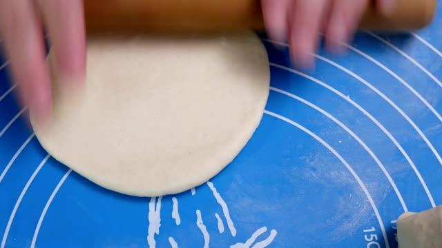 Bewegung der Menschen kneten den Teig und formen ihn mit ihren Händen, um Brötchen zu Hause zu dampfen – Video