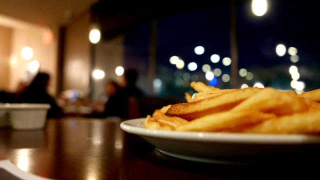 Motion of people ordering foods inside restaurant, focus on fries – Video