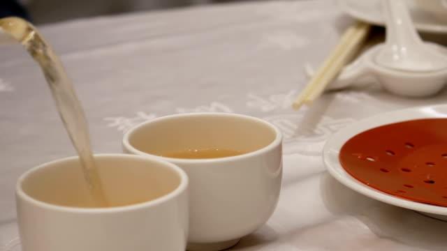 Bewegung von Menschen, die heißen Tee in chinesisches Restaurant gießen – Video