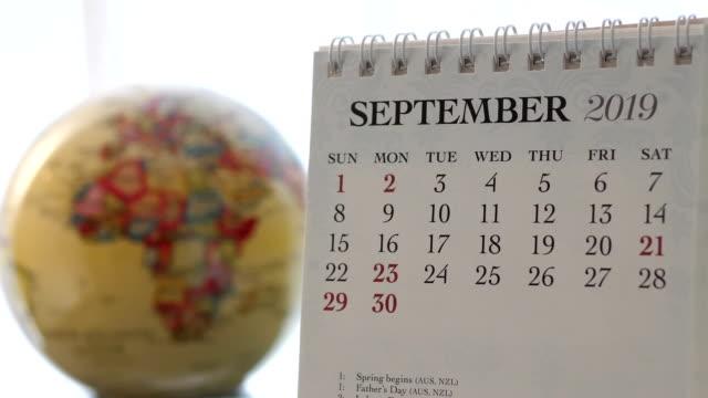 vídeos de stock, filmes e b-roll de movimento de setembro de 2019 calendário com borrão globo de terra girando fundo - setembro amarelo