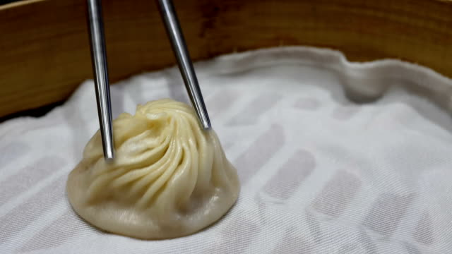 Motion of woman eating soup dumpling buns with chopsticks in restaurant video