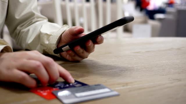 ruch kobiety wpisując numer karty kredytowej do zakupu prezentu na smartfonie - credit card filmów i materiałów b-roll