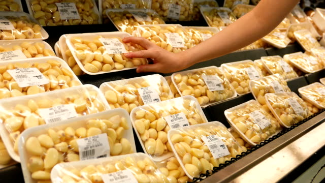 motion of woman's hand picking garlic inside superstore - aglio alliacee video stock e b–roll