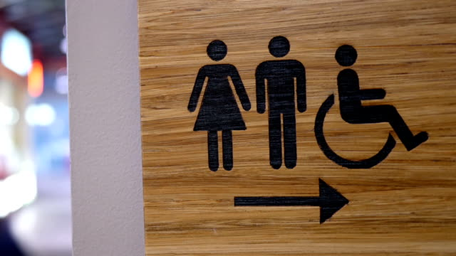 Motion of wooden man and woman washroom logo on wall inside Burnaby shopping mall