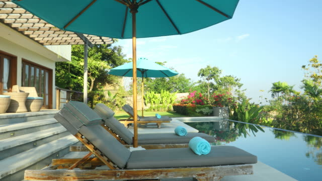 bewegung schwenken des eigentums luxuriöse villa mit pool - sun chair stock-videos und b-roll-filmmaterial