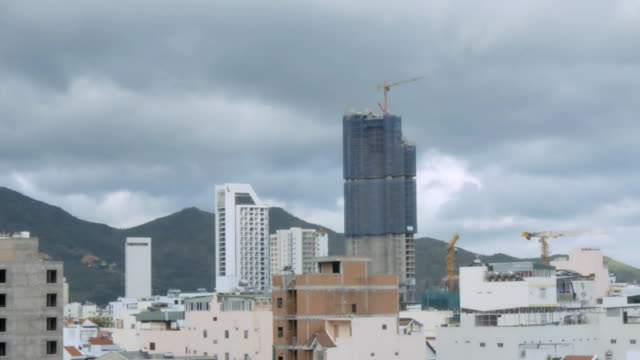 motion past skyscraper in city at hills timelapse - indochina stock-videos und b-roll-filmmaterial