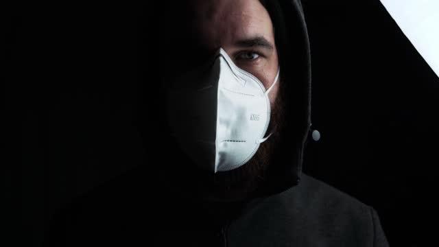 движение портрет человека носить kn95 лицевой маски для предотвращения covid19 на темном фоне, коронавирус. - covid testing стоковые видео и кадры b-roll